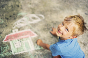 Boy drawing with sidewalk chalk