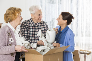 Senior couple packing house with caregiver