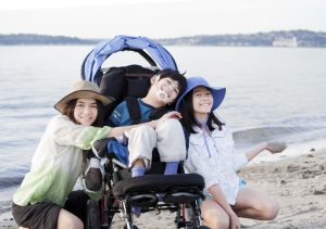 Sisters taking care of disabled brother on beach
