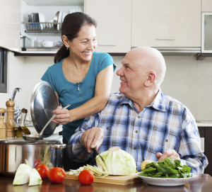 happy mature  couple cooking vegetarian lunch