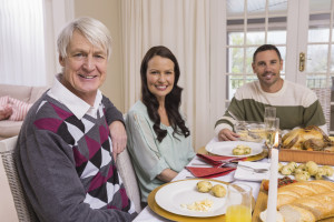 Elderly man having dinner with young couple