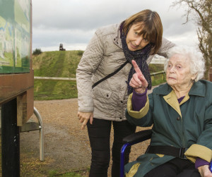 Elderly woman and caregiver looking at park map