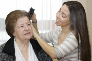 Elderly woman having hair brushed