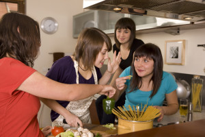 Group of young women cooking pasta