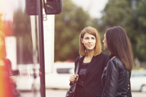 Two females waiting at bus stop